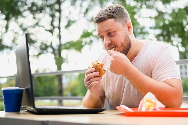 ノートパソコンを見ながら食べる若い男 無料写真