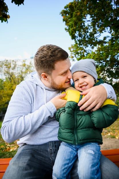 若い男が彼の足に男の子を保持 無料写真