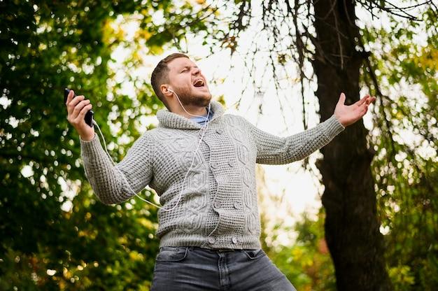 スマートフォンと公園でイヤホンを持つ男 無料写真