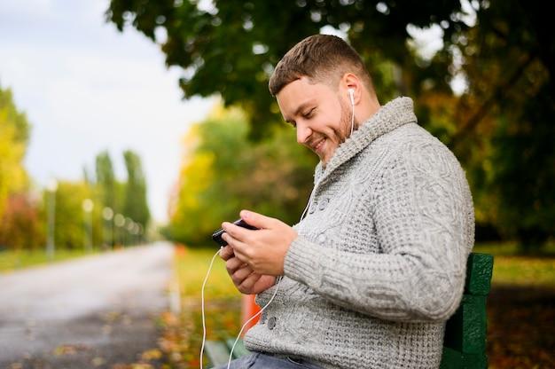 スマートフォンとイヤホンをベンチに幸せな男 無料写真