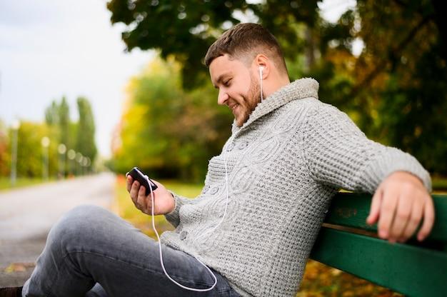 スマートフォンとイヤホンのベンチでスマイリー男 無料写真