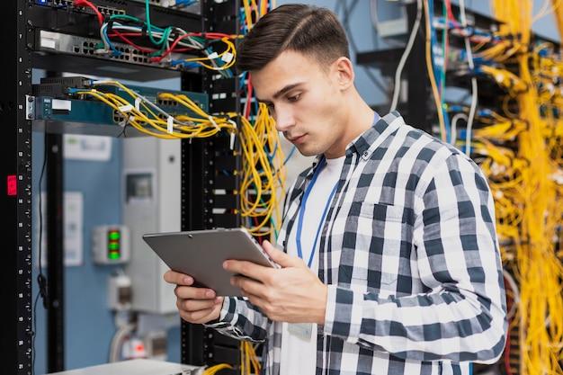 Молодой инженер с планшетом в серверной комнате среднего снимка Бесплатные Фотографии