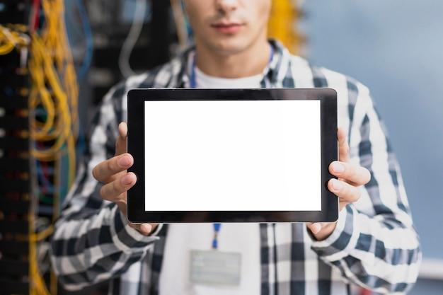 タブレットのモックアップを持つ若いエンジニア 無料写真