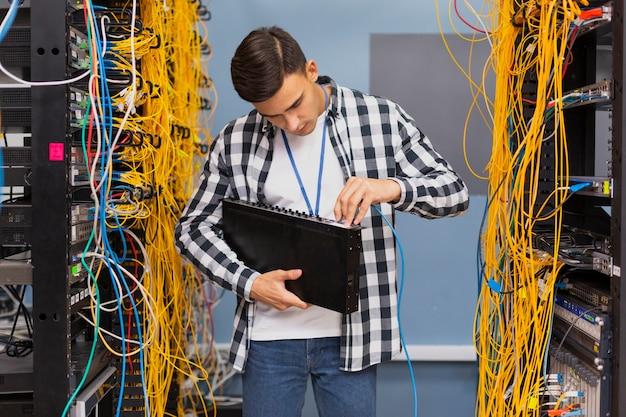 イーサネットスイッチを保持している若いネットワークエンジニア 無料写真