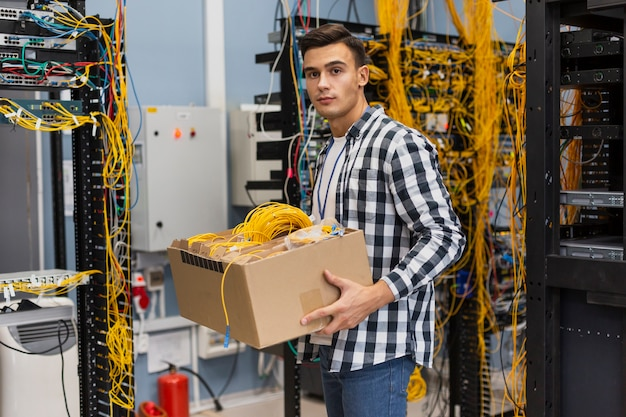 ワイヤーミディアムショットでボックスを保持している若い男 無料写真