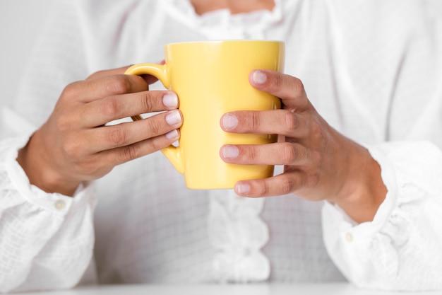 黄色のマグカップを保持しているクローズアップ手 無料写真