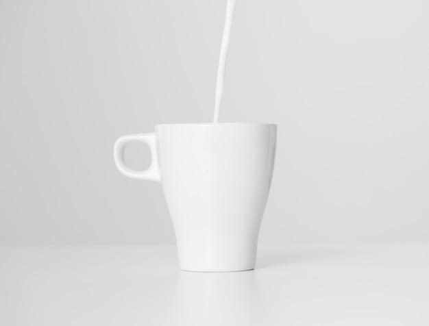セラミックカップに注ぐクローズアップミルク 無料写真