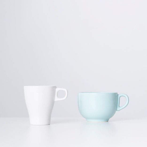 Вид спереди белая чашка и керамическая кружка Бесплатные Фотографии