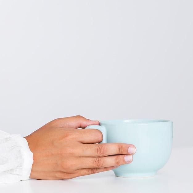 セラミックカップを持っているクローズアップ手 無料写真