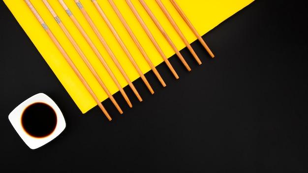 黄色と黒の背景に醤油ボウルと箸 無料写真