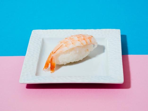 青とバラの背景にエビ寿司と白いプレート 無料写真