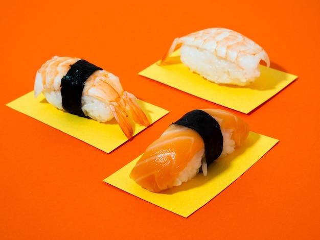 オレンジ色の背景にサーモンとエビの寿司 無料写真