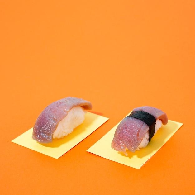 オレンジ色の背景にマグロ寿司 無料写真