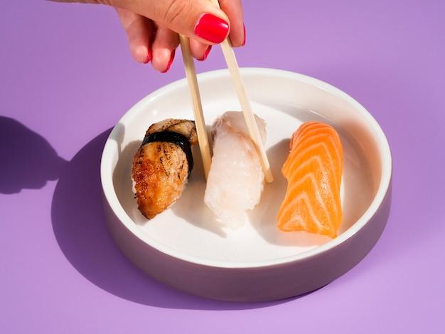 寿司皿からおいしい寿司を取る女性 無料写真
