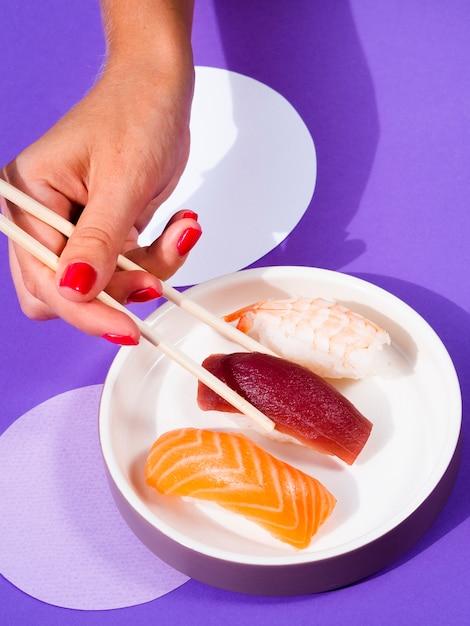 プレートから箸でマグロ寿司を選ぶ女性 無料写真