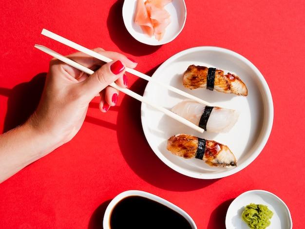 Женщина выбирает суши из белой тарелки Бесплатные Фотографии