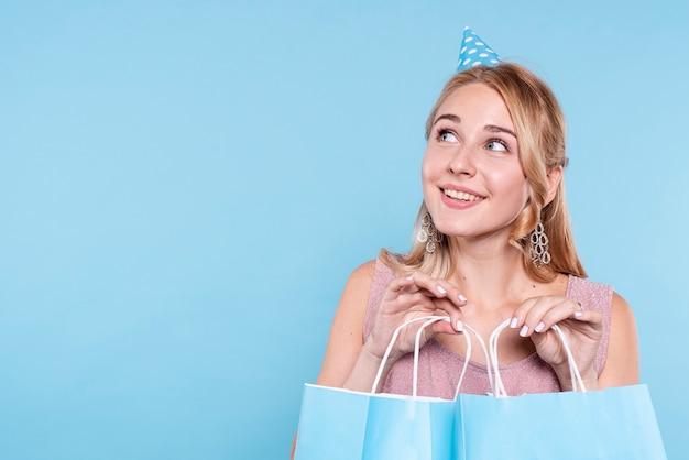ギフトとバッグを保持している誕生日パーティーでスマイリー女性 無料写真