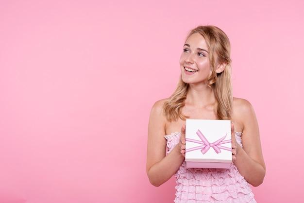 Смайлик молодая женщина, держащая подарок Бесплатные Фотографии