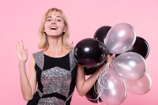 Красивая женщина держит букет из воздушных шаров Бесплатные Фотографии