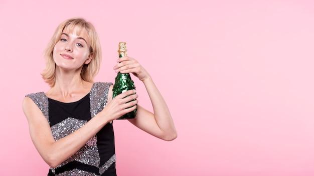 ピンクの背景にシャンパンのボトルを示す女性 無料写真