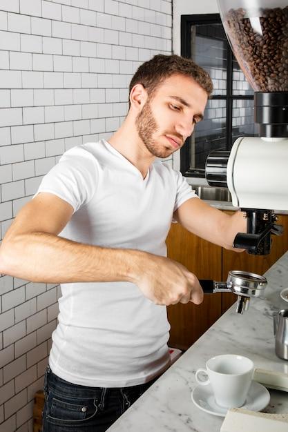 Молодой бариста делает чашку кофе Бесплатные Фотографии
