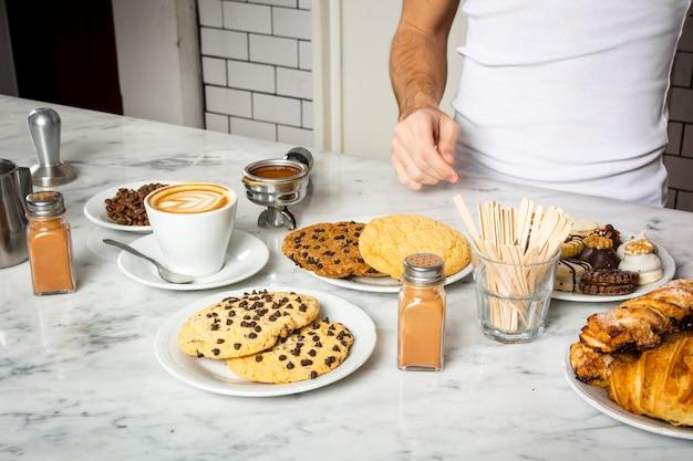一杯のコーヒーとカウンターの上のクッキーのプレート 無料写真