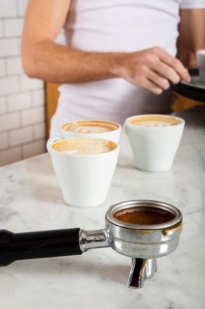 Портафильтр с молотым кофе и тремя чашками кофе Бесплатные Фотографии
