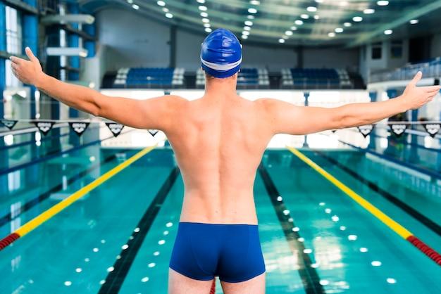 泳ぐ前にウォーミングアップの男性スイマー 無料写真