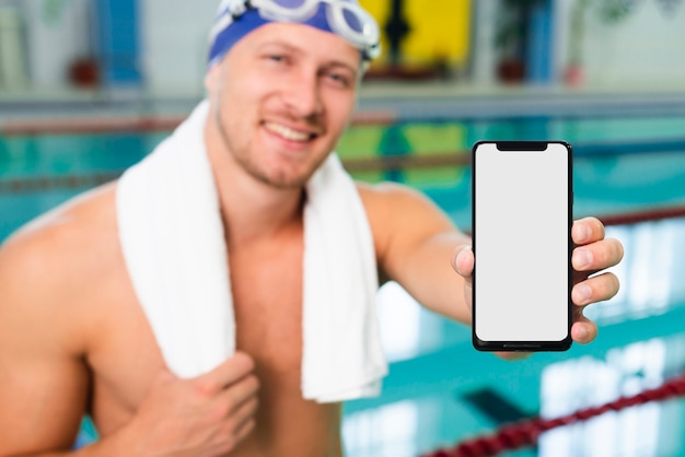 モバイルを保持しているプールで高角度の若い男 無料写真