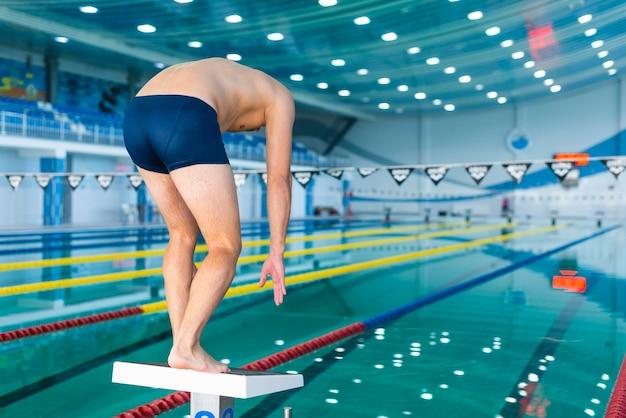 スイミングプールでジャンプする準備をして運動の男 無料写真