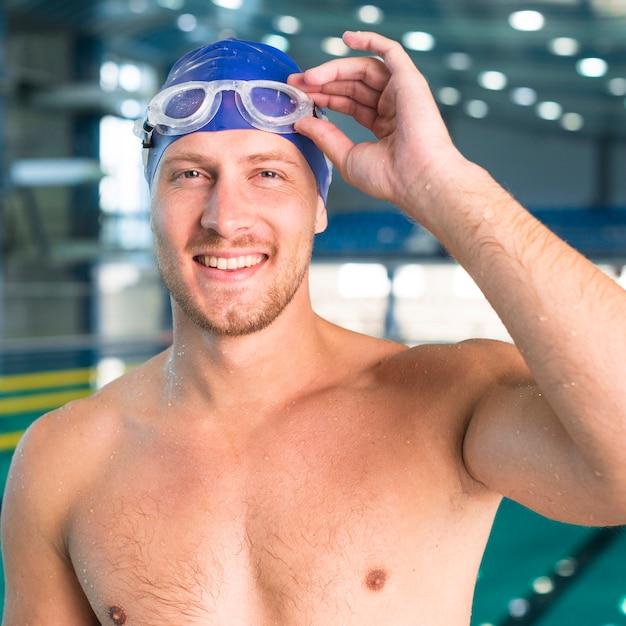 彼の水泳用ゴーグルを配置するハンサムな男 無料写真
