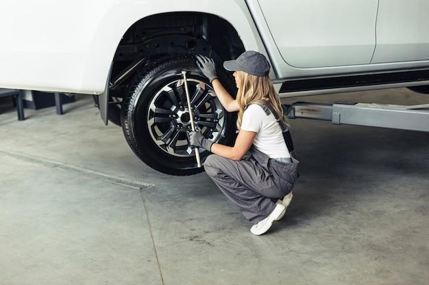 車のホイールを変更する高角度の女性メカニック 無料写真