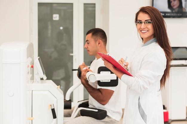 Улыбающиеся женщина-врач, проверка состояния пациента Бесплатные Фотографии