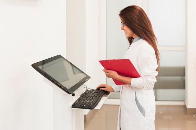 クリップボードを押しながらコンピューターで作業して医師 無料写真
