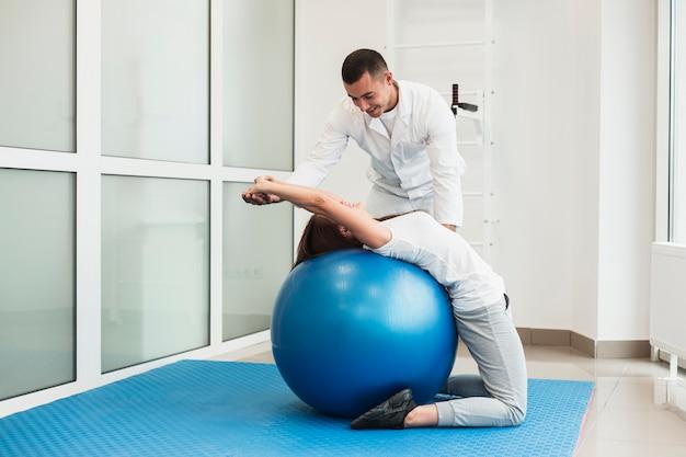 Доктор растяжения пациента на упражнение мяч Бесплатные Фотографии