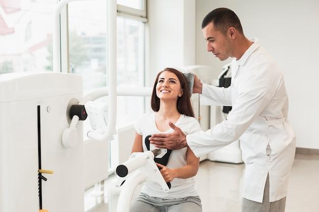 Доктор регулируя голову пациента в медицинской машине Бесплатные Фотографии