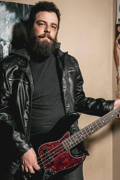 Бородатый мужчина играет на бас гитаре Бесплатные Фотографии