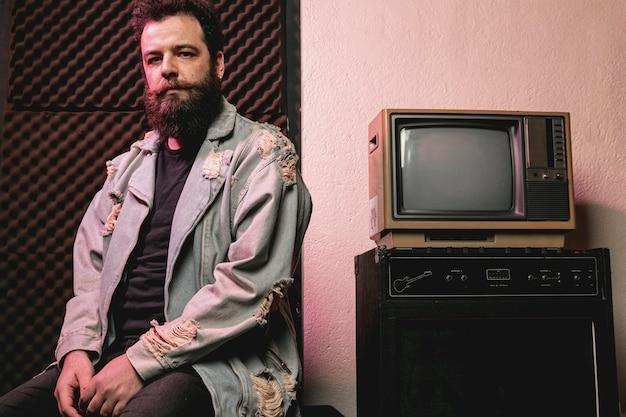Хипстерский человек, расположенный рядом со старинным телевизором Бесплатные Фотографии