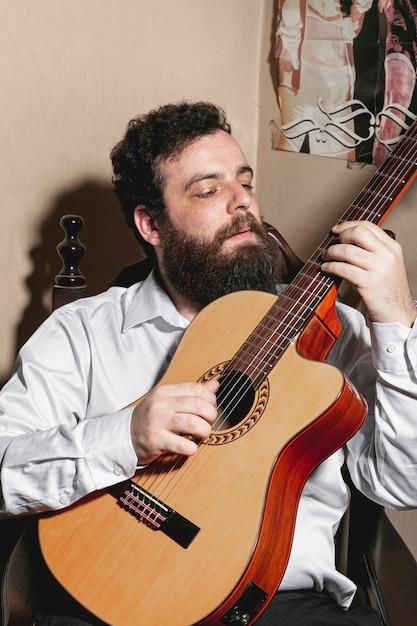 Портрет человека, играющего на акустической гитаре Бесплатные Фотографии