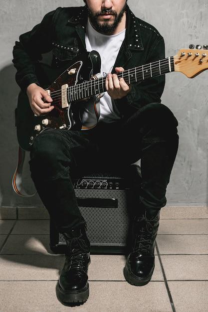 アンプの上に座って、ギターを弾く男 無料写真