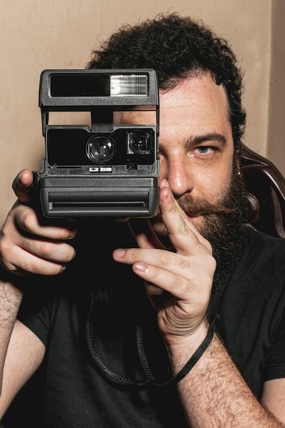 ビンテージカメラを使用して流行に敏感な男の肖像 無料写真