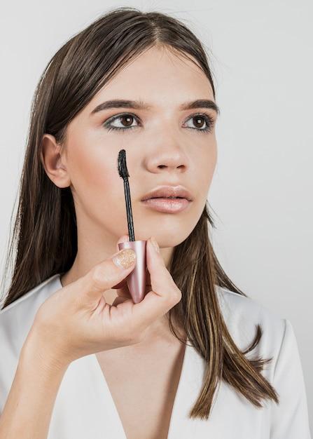 若いモデルにマスカラーを適用する女性 無料写真