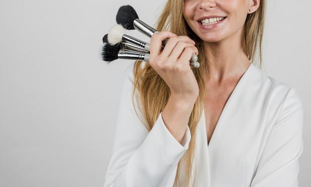 Счастливый художник держит макияж кисти Бесплатные Фотографии