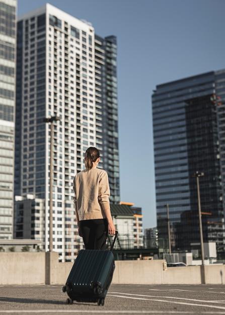 都市のスーツケースを持つ若い女性 無料写真
