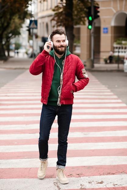 Полный выстрел парень с наушниками пересекает улицу Бесплатные Фотографии