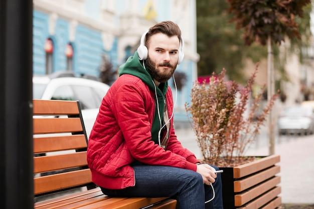 ヘッドフォンと暖かい服を着たミディアムショットの男 無料写真