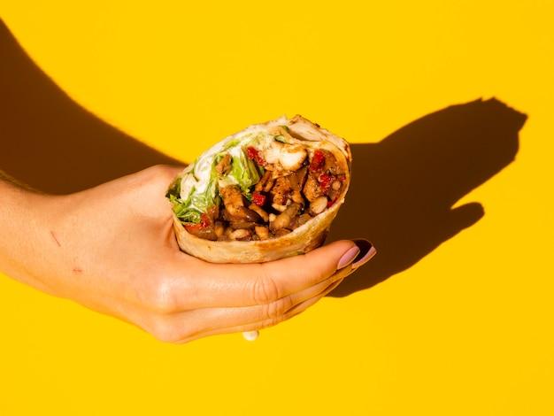 Крупным планом лицо, занимающее вкусные буррито Бесплатные Фотографии
