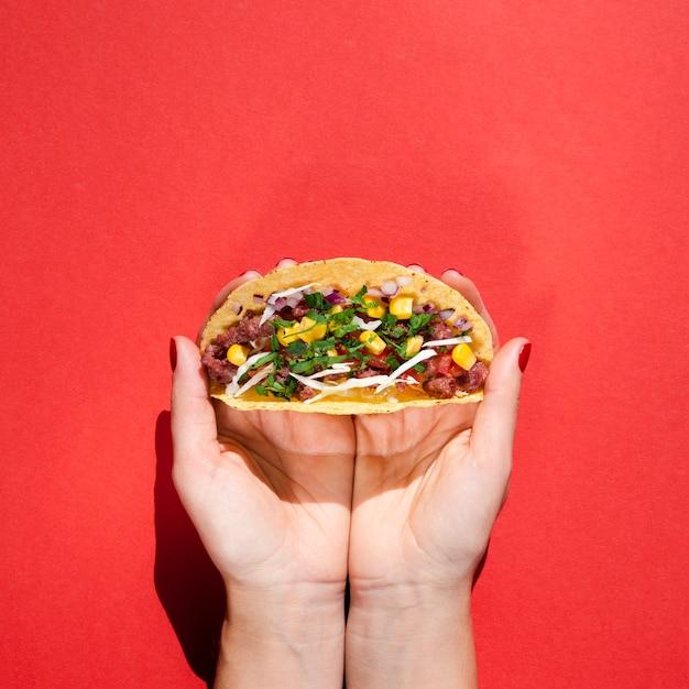 Человек крупным планом с вкусной мексиканской едой и красным фоном Бесплатные Фотографии