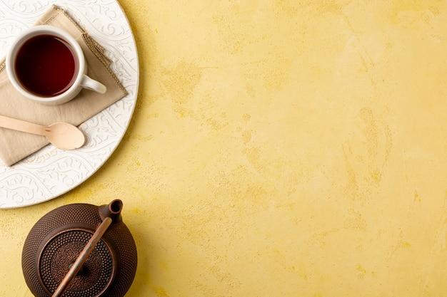 黄色の背景にティーポットとトップビューフレーム 無料写真