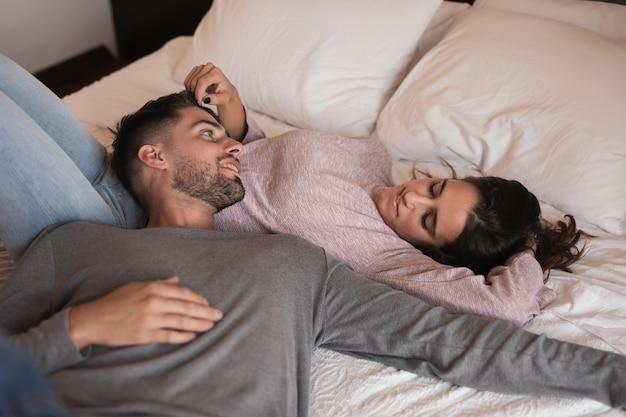 ベッドに敷設の美しいカップル 無料写真
